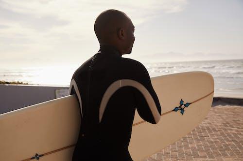 Black man with surfboard on coast of ocean