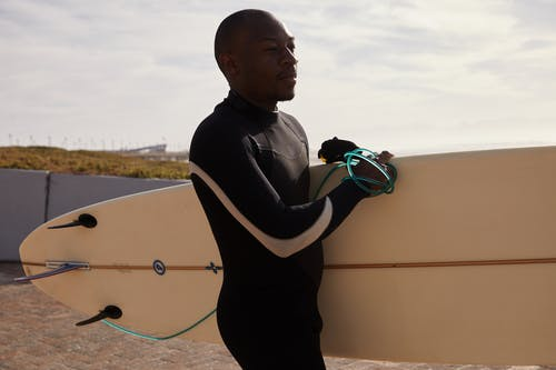 Pensive black man with surfboard against sky in daytime
