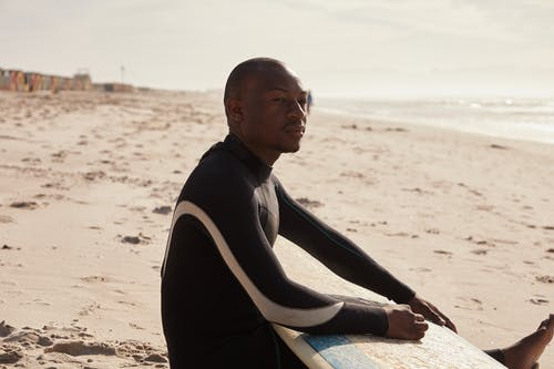 Side view of slim African American surfer in black wetsuit looking away while chilling on sandy shore of ocean in daytime in sunlight