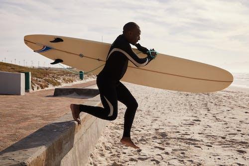 Schwarzer Surfer, Der Tagsüber Mit Surfbrett Zum Ozean Läuft