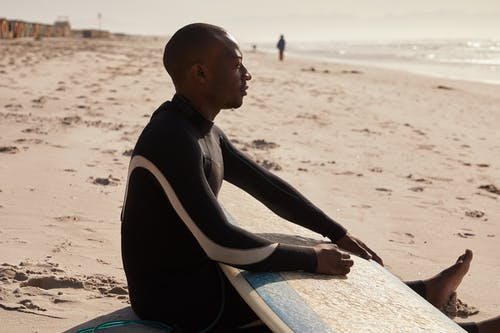 Side view of African American surfer in dark wetsuit thoughtfully looking away while lounging on sandy shore of endless ocean in sunlight