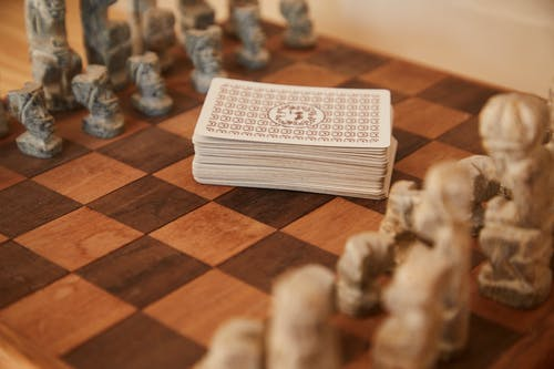 Chessboard with chess pieces and game of cards