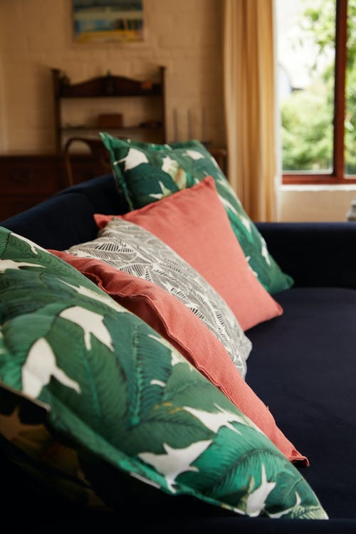 Soft cushions with bright design placed on comfortable couch in modern room in daylight