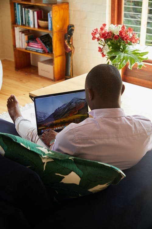 Black man resting in cozy sofa and browsing laptop