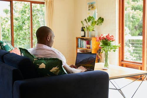 Black man studying and reading on laptop
