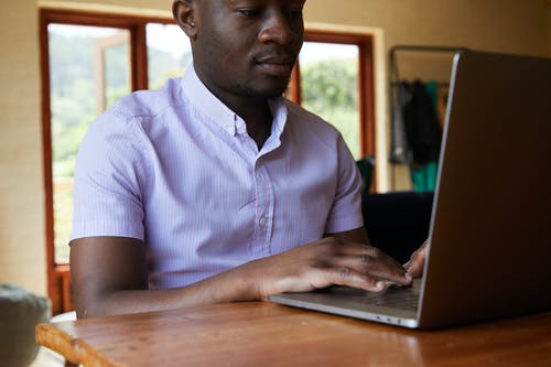 Black man chatting on internet in laptop
