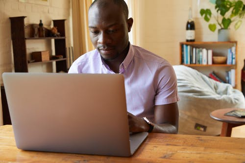 Black man working on important project on laptop