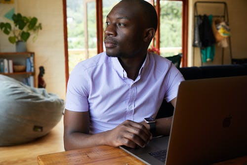 Serious African American male freelancer in formal wear sitting at wooden table while browsing netbook and looking away