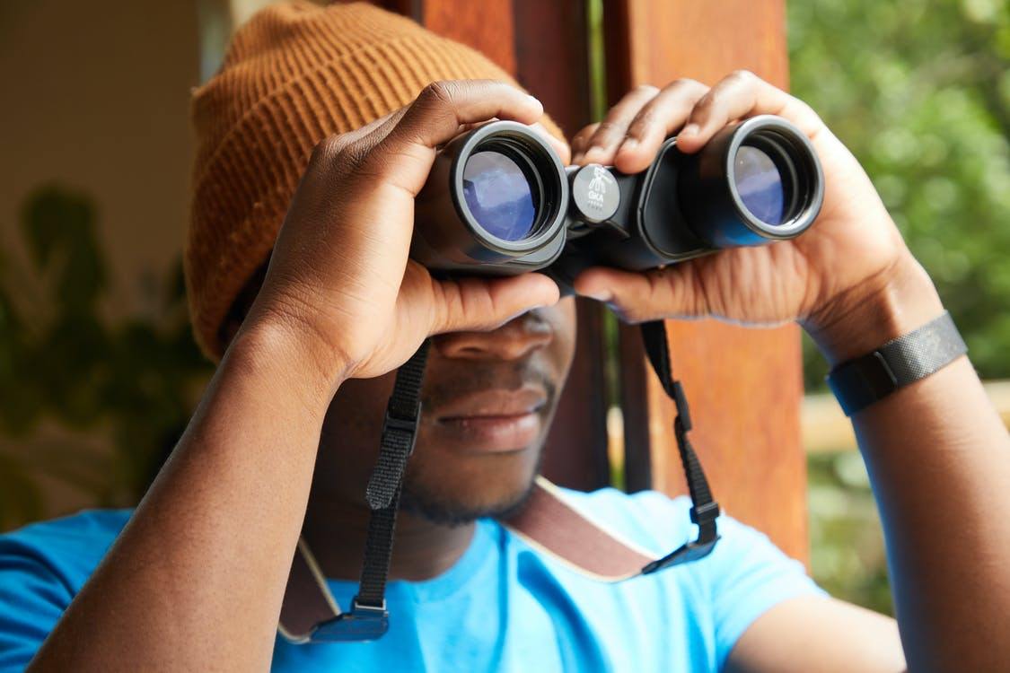 Faceless African American male in beanie looking through binoculars while standing near opened window