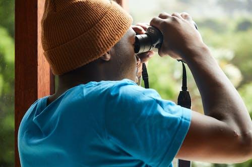 Black man with binoculars at home