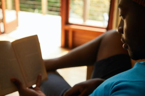 Crop African American male in casual clothes sitting on sofa and reading book while resting at home