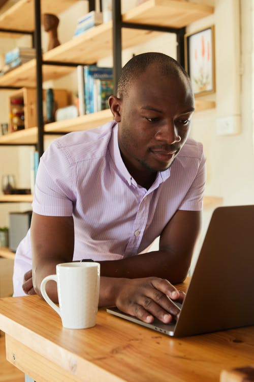 Young African American male in shirt sitting at table with netbook and cup of beverage while working at home
