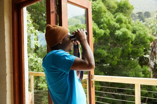 African American man with binoculars near balcony