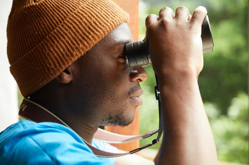 Side view of anonymous African American male in trendy hat looking through binoculars while standing against opened window
