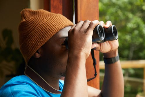 Unrecognizable male tourist with binoculars standing near window and observing picturesque scenery of forest