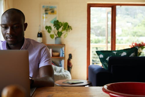 Concentrated African American male freelancer sitting at wooden table and browsing netbook while working online