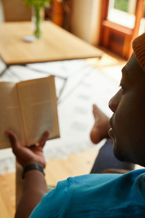 Crop African American male sitting on couch and reading book while spending weekend at home