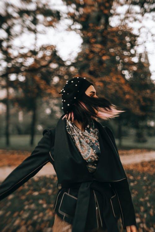 Woman in Black Coat Standing Near Brown Trees