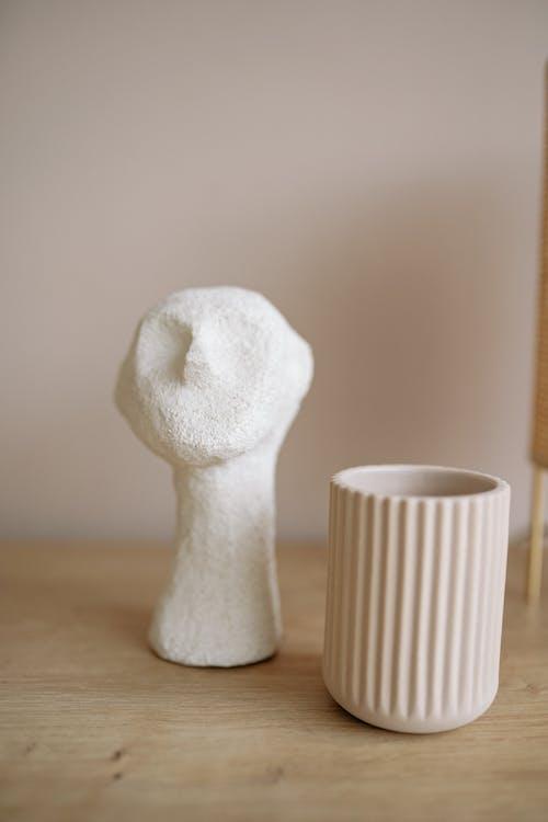 A Close-Up Shot of Ceramic Figurine and a Vase