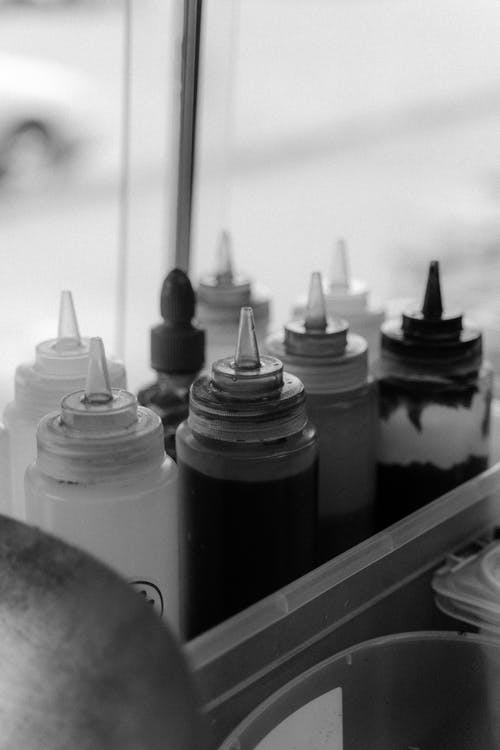 A Grayscale of Condiments in Squeeze Bottles