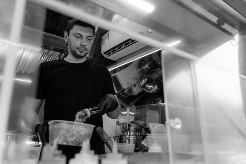 A Grayscale of a Man Wearing a Black Shirt Working in a Kitchen