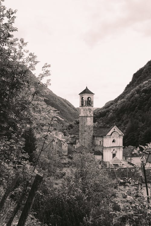 Black and white medieval shabby stone temple located among trees and hills in village
