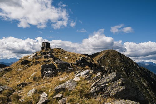 High rocky peak of mountain with rough uneven stones under cloudy blue sky in sunny day