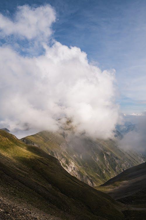 Clouds over high mountain peak in wild terrain