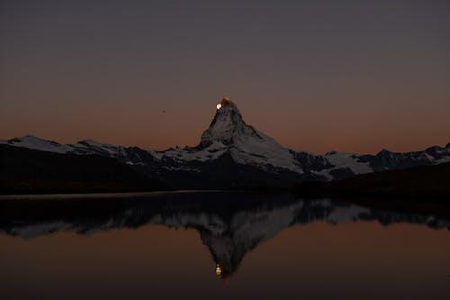 High mountain range reflecting on lake surface under moon shining on clear sky