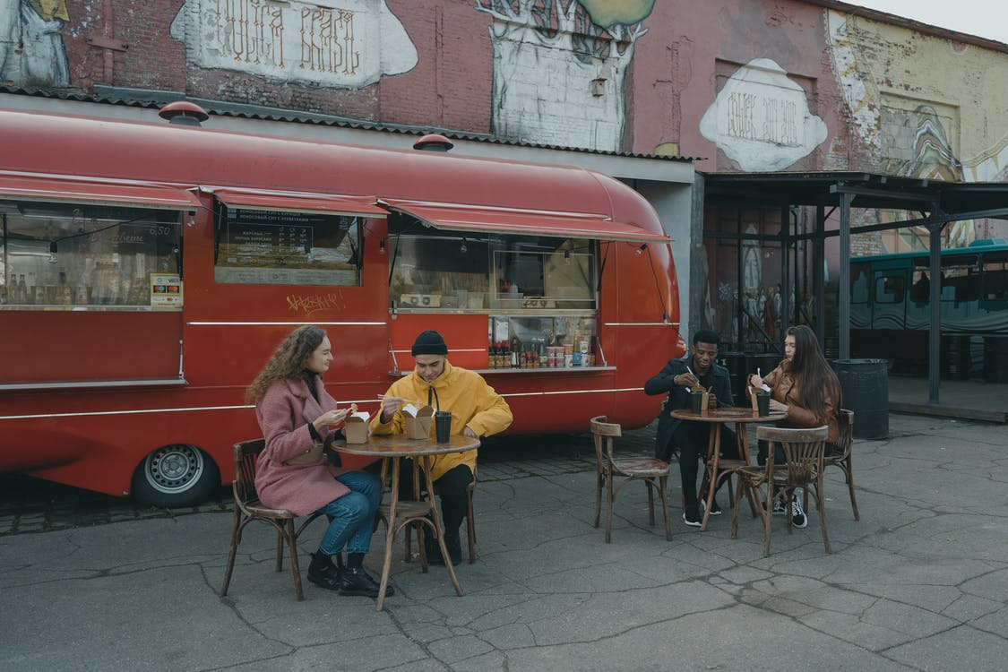People Sitting on Chair Near Red Bus