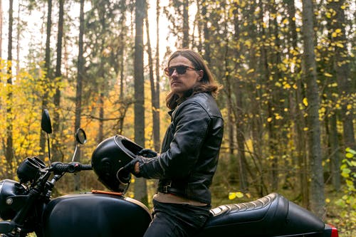 Woman in Black Leather Jacket Riding on Black Motorcycle
