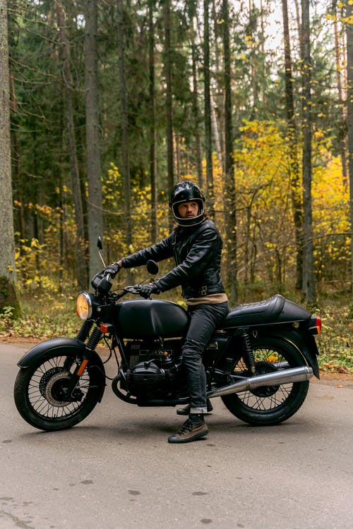 Man in Black Leather Jacket Riding Black Motorcycle in Forest