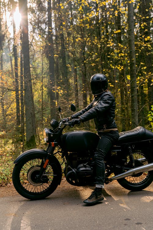 Man in Black Leather Jacket Riding Motorcycle in Forest