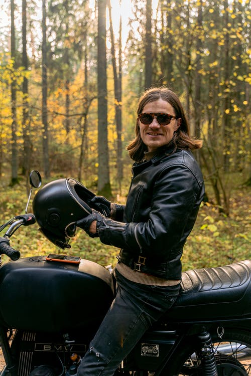 Woman in Black Leather Jacket and Black Pants Riding on Black Motorcycle