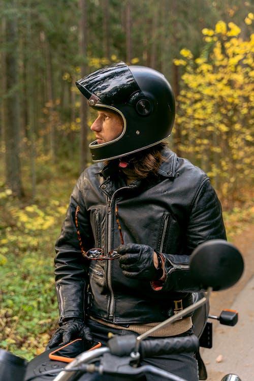 Man in Black Leather Jacket Wearing Helmet Riding Motorcycle