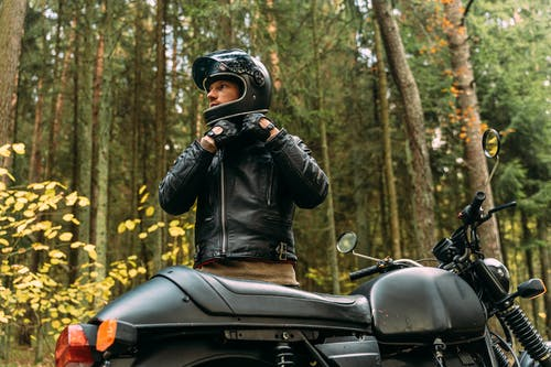 Man in Black Leather Jacket Riding on Black Motorcycle