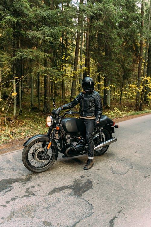 Man in Black Jacket Riding Black Motorcycle on Road