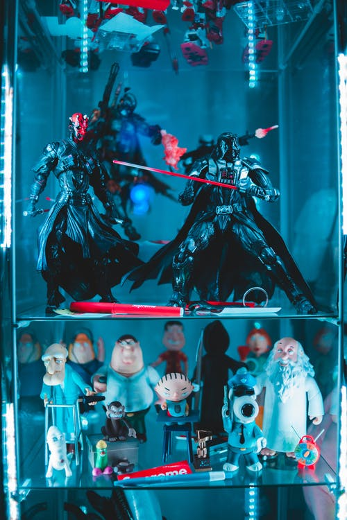 Collection of different assorted figures from movies and cartoons placed in glass shelves with neon light