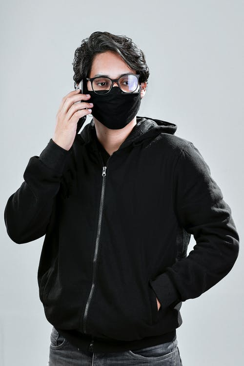 A Man Wearing a Face Mask while Talking on the Phone