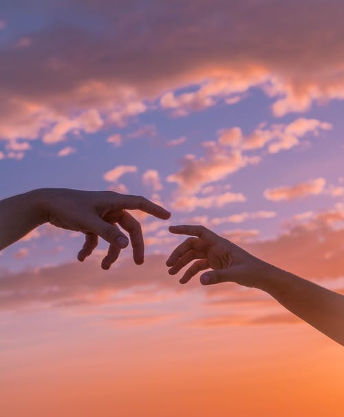 Crop anonymous people pulling hands to each other against bright sunset sky with clouds