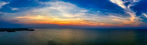 Endless ocean under colorful sky at sunset