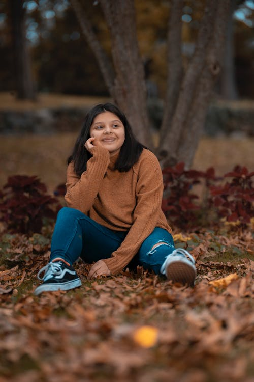 Woman in Brown Sweater and Blue Pants Sitting on Dried Leaves