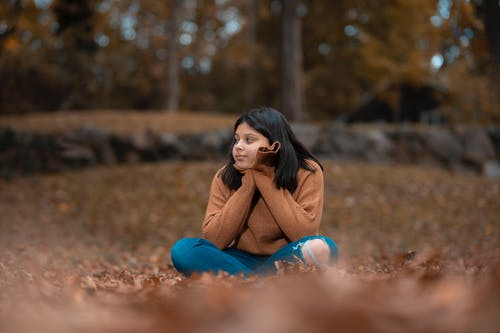 Woman in Brown Long Sleeve Shirt and Blue Denim Jeans Sitting on Ground With Water