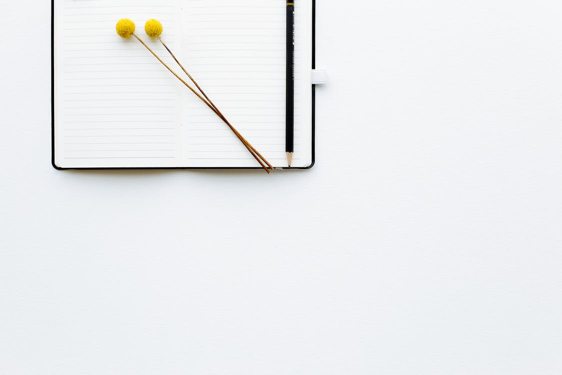 Top view composition of pencil and creative bookmarks placed on opened diary with blank sheets on white desk