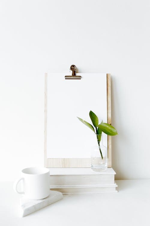 Composition of clipboard with empty sheet placed on stacked books near white mug and green plant leaf