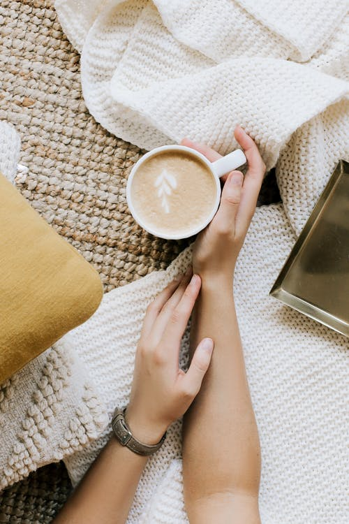 Top view crop unrecognizable female resting hands with cup of freshly brewed cappuccino on cozy soft cloth