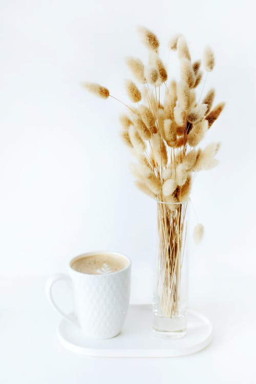 Bouquet of dried plants placed near cup of coffee