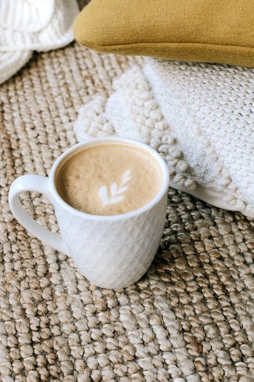 From above white ceramic mug of fresh hot cappuccino placed on soft knitted plaid near pillows