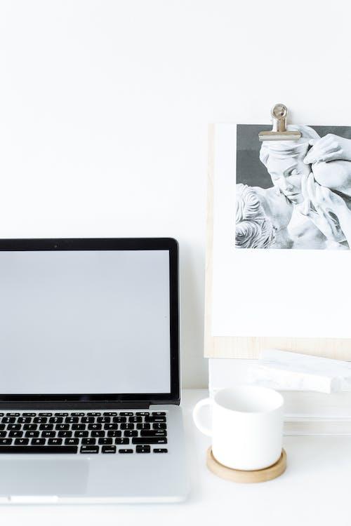 現代打開筆記本電腦在杯子附近的桌子上
