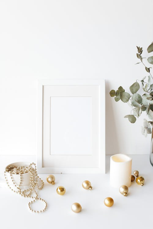Empty photo frame on desk near Christmas tree decorations
